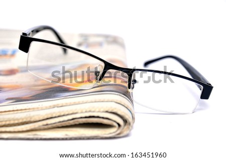 Black glasses on a newspaper  - stock photo