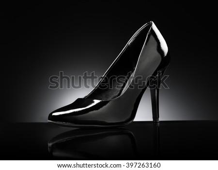 Black glossy ladies stiletto heel pump on black reflective background. - stock photo
