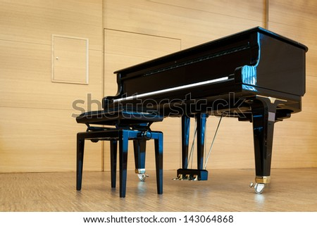 black grand piano with music stool at wooden stage - stock photo