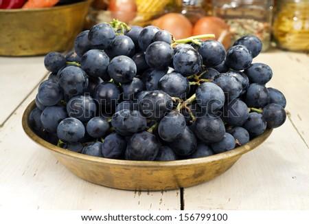 Black grape in copper tray - stock photo