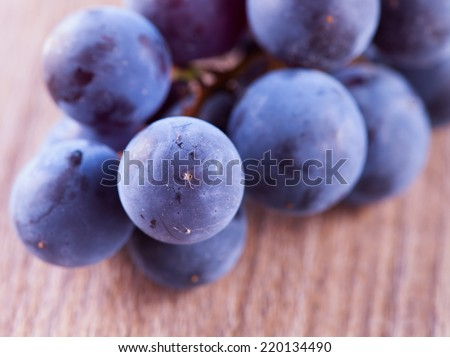 Black grape over table, strict close up - stock photo