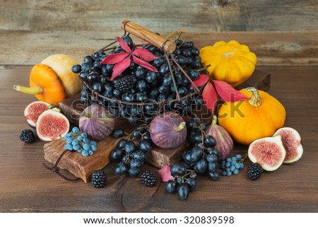 Black grapes in a vintage metal basket with wooden handle and ripe figs, red raspberries, orange pumpkin and blackberries with autumn leaves on the wooden background - stock photo
