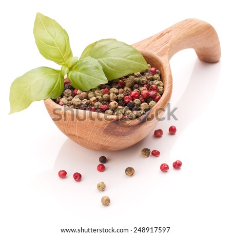 Black peppercorn in a wooden bowl isolated on white