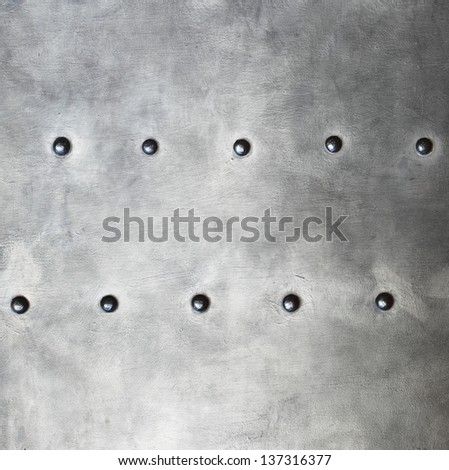 Black grunge metal plate or armour texture with rivets as background