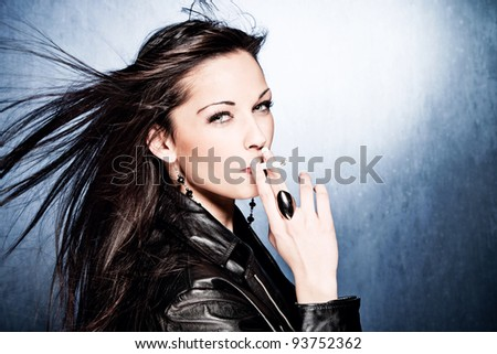 black hair woman in leather jacket, smoking, studio shot - stock photo