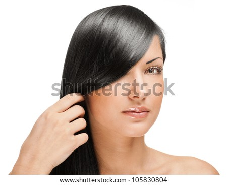 black haired beautiful woman holding her long straight hair - stock photo