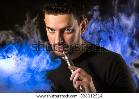 Black haired handsome man with e-cirarette in a blue lighted vapor - stock photo