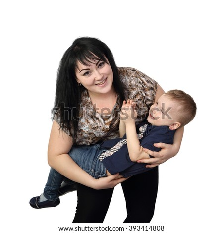 Black haired woman holds small boy on hands - Mother and little son playing isolated on white background
