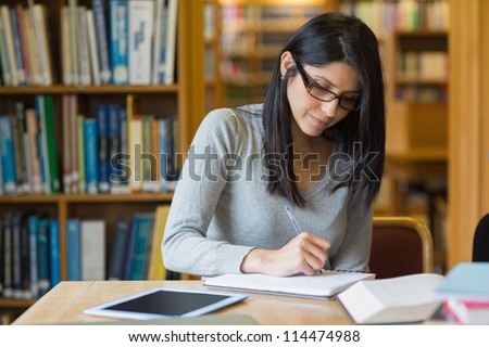 Black-haired woman studying in the library - stock photo