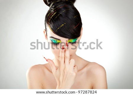 black haired young woman with great colorful makeup, studio shot - stock photo