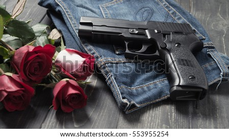 Black hand gun lying on blue jeans pants beside red rose bouquet with dark wood background.