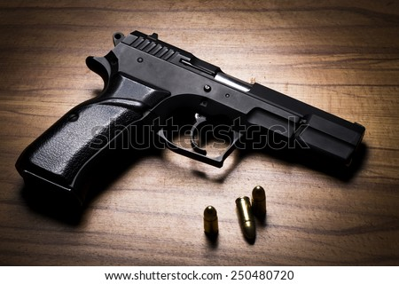 Black Handgun and bullets on a wooden background. - stock photo