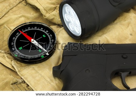 Black Handgun, Magnetic Compass And Led Tourch On The  Faded Green Backpack Background Close-up - stock photo