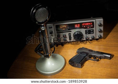 Black handgun on the table with a microphone and two way radio - stock photo
