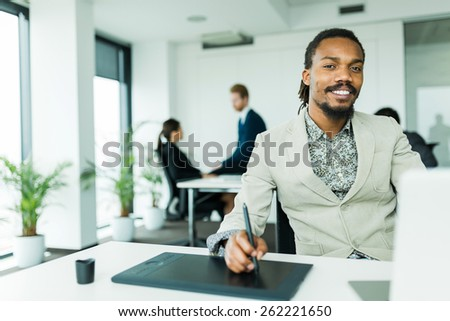 Black handsome graphics designer  with dreadlocks using digitizer in a well lit, tidy office environment  while his colleagues are working overtime in the background - stock photo
