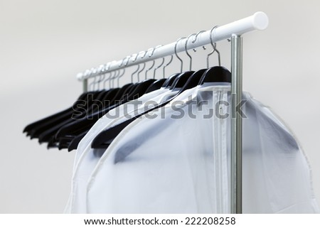 Black hangers on rack with white wear bags - stock photo