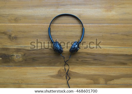Black Headphones on Wood Table Background Top View Headset Earphone Technology Listen to Music