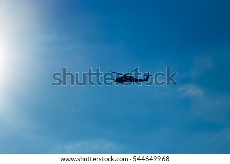 Black helicopter flying into the sun