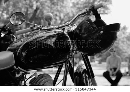 Black helmet hung on a black motorcycle. Black and white photo.