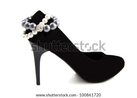 Black high heel shoe with bracelet pearls isolated over white - stock photo