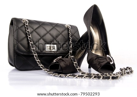 Black high heel women shoes and a bag on white background. - stock photo