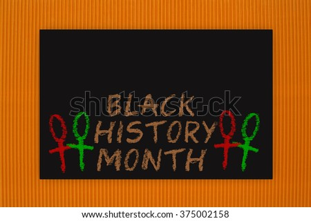 Black History Month Blackboard hanging on orange textured background pattern - stock photo