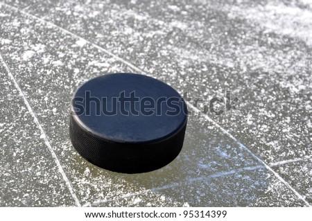 black hockey puck on ice rink - stock photo