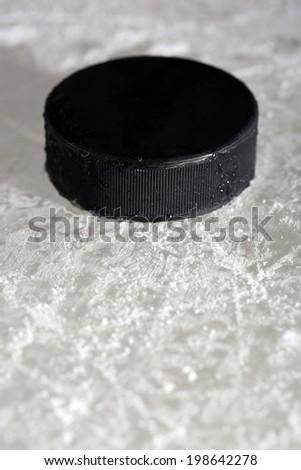 Black hockey puck on ice rink background - stock photo