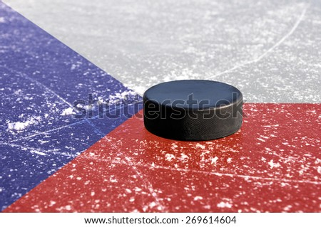 Black hockey puck on ice rink with Czech flag. - stock photo