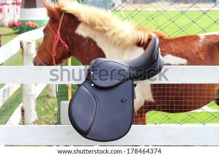 black horse saddle  on wood fence - stock photo