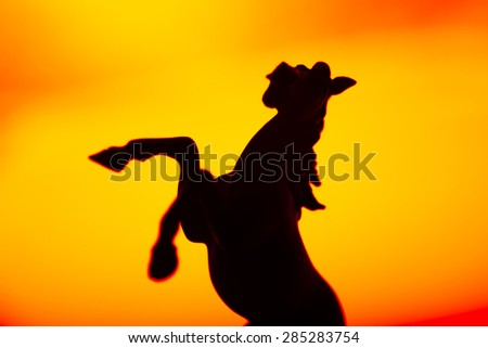 Black horse silhouette over yellow background - stock photo