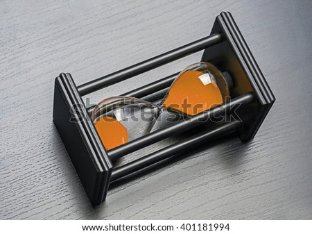 Black hourglass on black background. Close up - stock photo