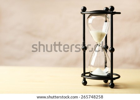 Black hourglass on wooden background