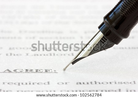 black ink pen over a printed agreement - stock photo