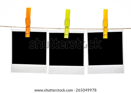 Black instant photo, hanging on the clothesline, isolated on white background. - stock photo