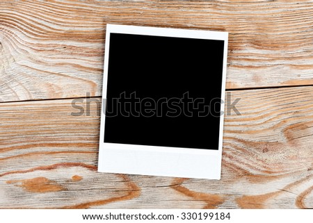 Black instant photo on a wooden background. Old vintage photo card and old table. Photo card background. - stock photo