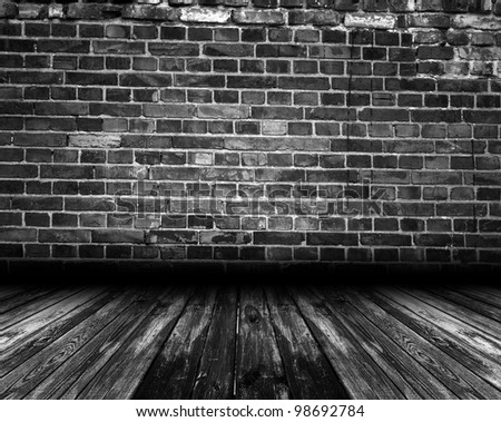 Black interior room with brick wall and wooden floor - stock photo