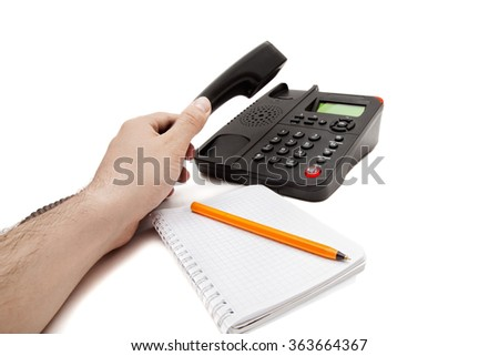 Black IP phone, notebook and pen on white background