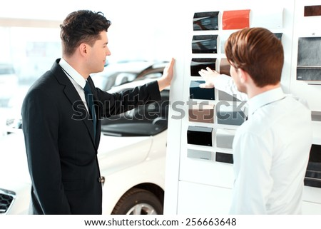 Black is perfect. Rear view of a handsome business man and sales assistant choosing the color of the new car by the colour palette in dealership - stock photo