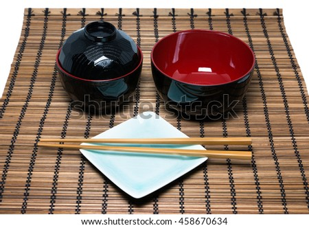 Black Japanese bowl and chopsticks on the bamboo mat