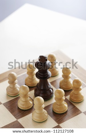 Black king surrounded by white pawns on chessboard - stock photo