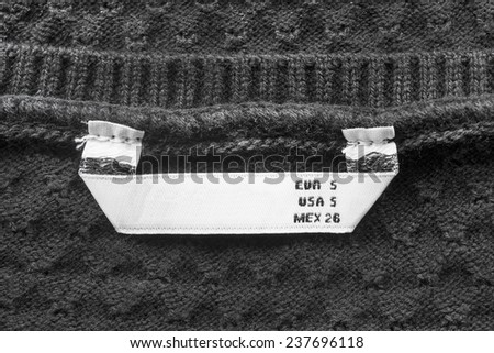 Black knitted cloth with white S size label as a background - stock photo