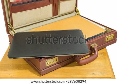black laptop and brown envelope in opened old vintage brown briefcase on wood table isolated - stock photo