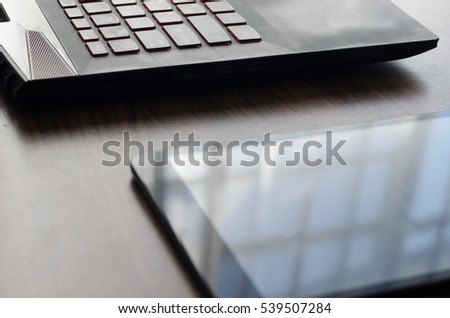 Black laptop and tablet on wood table