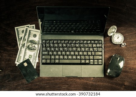 Black laptop on wood with Banking card, cash and clock. Image for internet shopping, fast electronic banking and web payment. - stock photo