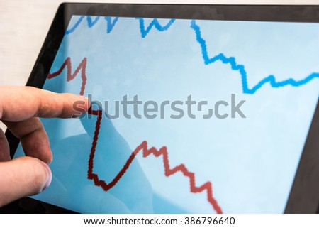 Black laptop with business charts on screen, on white table in office. Hand using the touchscreen.
