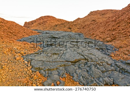 Black Lava Flow on Red Volcanic Ash on Santiago Island in the Galapagos - stock photo