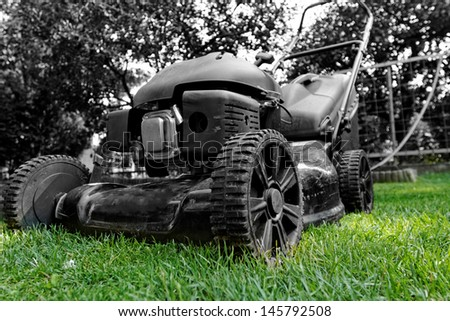 Black lawnmower in the garden lawn the grass with fuel engine bw color - stock photo