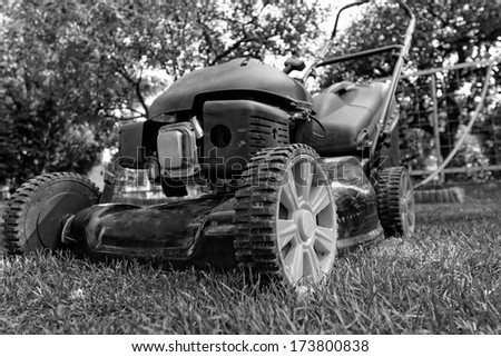 Black lawnmower in the garden lawn the grass with fuel engine in bw - stock photo