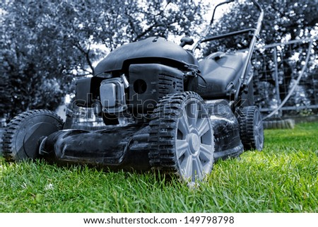 Black lawnmower in the garden lawn the grass with fuel engine with blue filter - stock photo